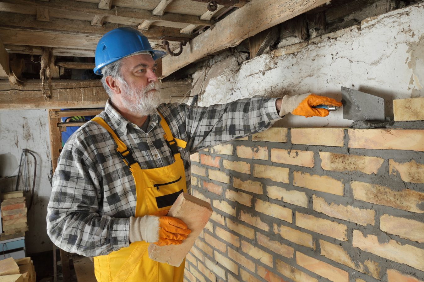 Worker building brick wall in old barn
